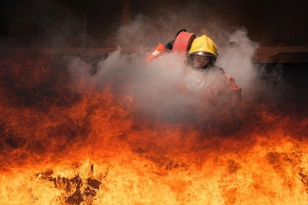 Training voor brandweerlieden, teamoefening voor het vechten met vuur in noodsituaties. een brandweerman draagt een waterslang die door de vlam loopt