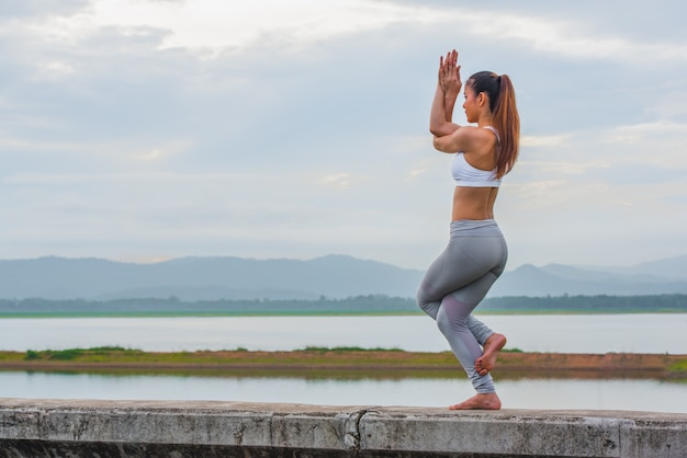 Training yoga, jonge vrouw doet yoga oefening op de muur in prachtige bergmeren