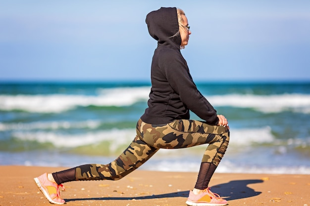Trainingsconcept crossfit fitness workout sport en levensstijl. vrouw in hoodie, legging. gezond en sport concept. buitensportactiviteiten