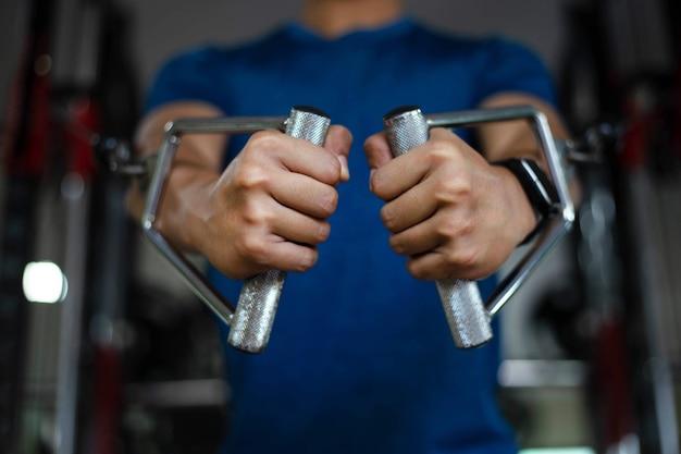 Trainingsgymnastiekconcept een gespierde mannelijke tiener die fitnessapparatuur gebruikt die zich naar voren duwt om zijn borst te ontwikkelen.