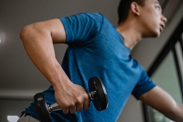 Trainingsgymnastiekconcept een jonge volwassene die zijn gespierde sterke arm gebruikt om een halter op en neer te tillen in de sportschool.