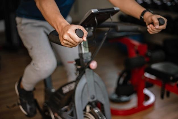 Trainingsgymnastiekconcept een mannelijke tiener die cardiotraining doet op een fietsmachine in de sportschool als zijn gezonde routine.
