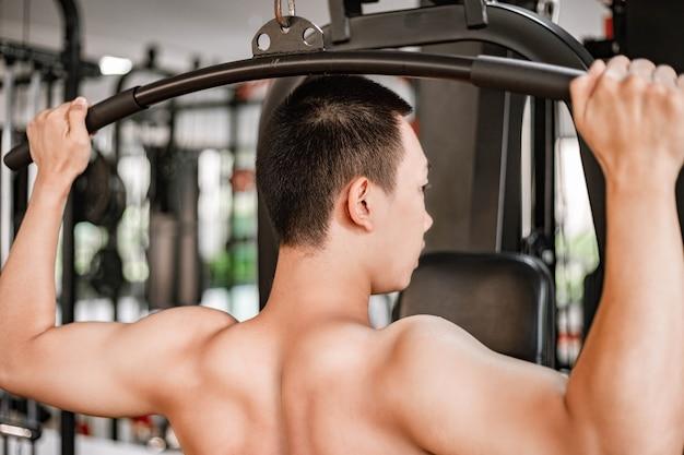 Trainingsgymnastiekconcept een mannelijke tiener die fitnessapparatuur gebruikt en zijn beide gespierde armen tegen de machine trekt.