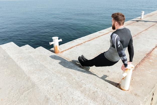 Trainingsoefening in de buurt van de zee. man doet push-ups. achteraanzicht