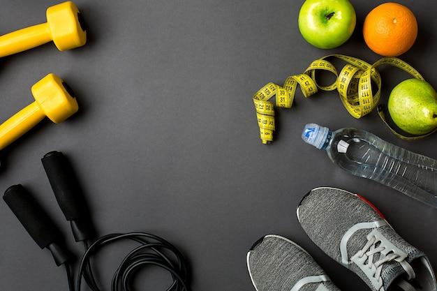 Trainingsplan met fitness eten en apparatuur op grijze achtergrond bovenaanzicht