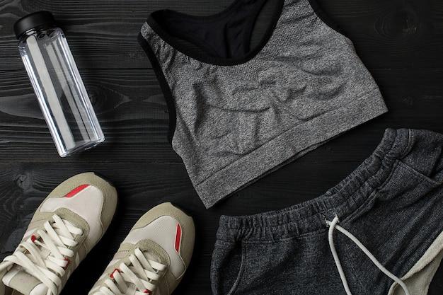 Trainingsplan met fitnessvoedsel en apparatuur op een donkere achtergrond bovenaanzicht
