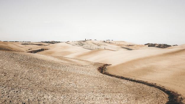 Traject in een woestijn die leidt naar de stad onder de heldere hemel