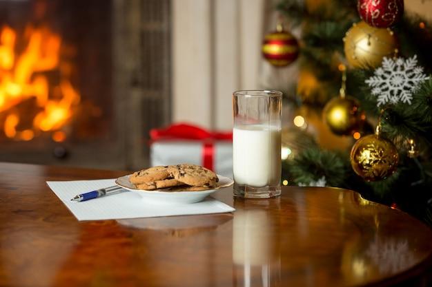 Traktaties en brief aan de kerstman op houten tafel naast kerstboom en brandende open haard