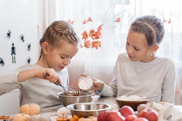 Traktaties en voorbereidingen voor de viering van halloween. schattig klein meisje voegt bloem toe aan het bakken van koekjesdeeg voor halloween in de keuken.