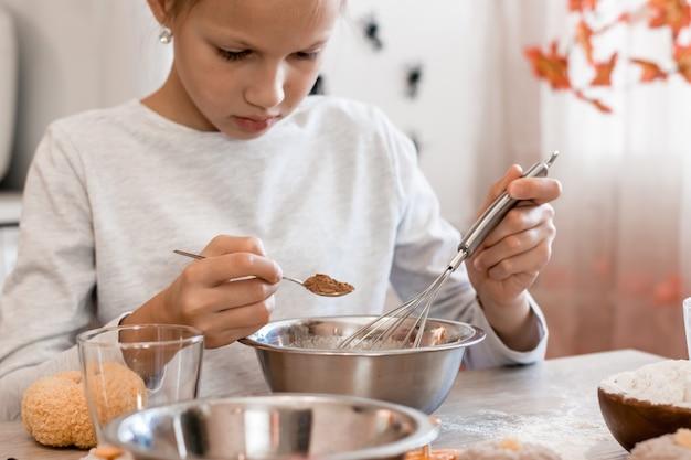 Traktaties en voorbereidingen voor de viering van halloween. schattig klein meisje voegt gember toe aan het bakken van koekjesdeeg voor halloween thuis keuken.