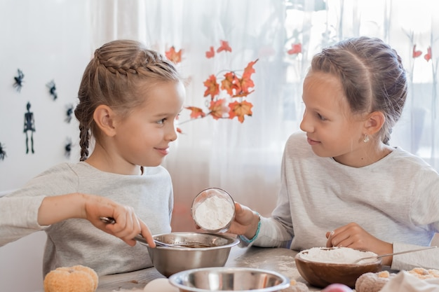 Traktaties en voorbereidingen voor de viering van halloween. twee meisjes bereiden halloween-koekjes in het deeg voor het bakken in de keuken.