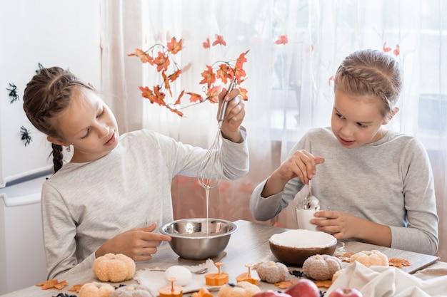 Traktaties en voorbereidingen voor de viering van halloween. twee schattige zussen die peperkoekdeeg voorbereiden voor het bakken van koekjes voor halloween in de thuiskeuken.