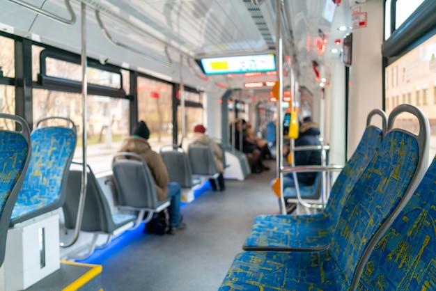 Tram interieur met passagiers.