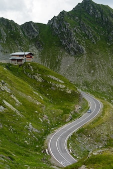 Transfagarasan bergweg met klein gebouw op rots, roemeense karpaten