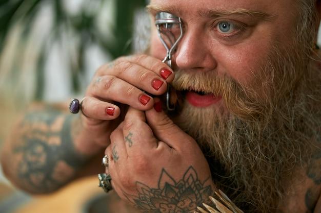 Transgender getatoeëerde man in een kamer met cosmetica