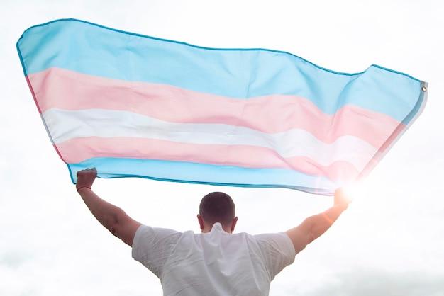 Transgender man met zwaaiende transgender vlag, concept foto over mensenrechten, gelijkheid in de wereld