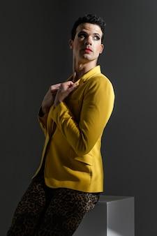 Transgender persoon die gele jas draagt die zijwaarts staat
