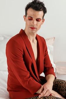 Transgender persoon draagt rode jas en zittend op het bed