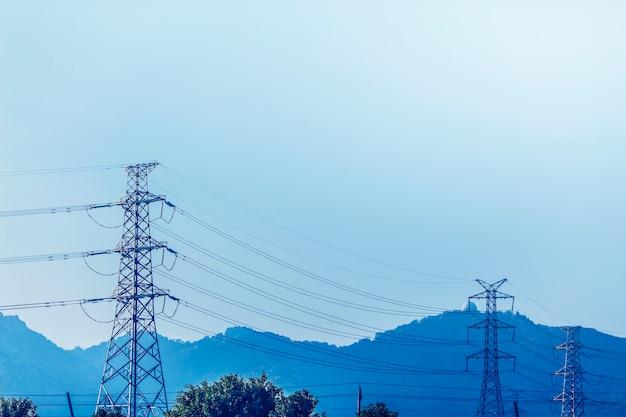 Transmissie van elektriciteit pyloon aftekenen tegen de blauwe hemel bij d