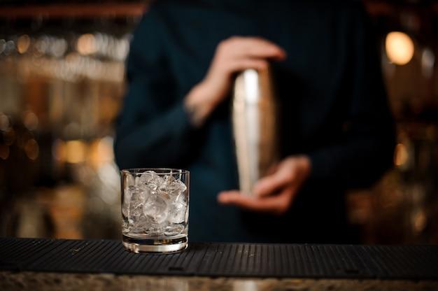 Transparant cocktailglas gevuld met ijsblokjes op de balk