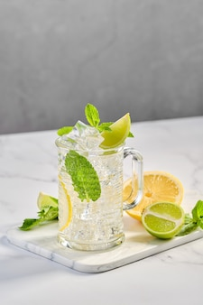 Transparant glas citroen, limoen en munt koude limonade op marmeren tafel
