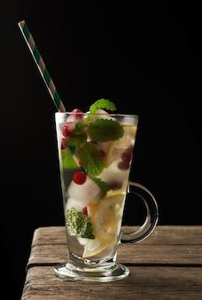 Transparant glas met limonade en stukjes ijs, rode bessen en papieren kokers, een verfrissend zomerdrankje op een zwarte achtergrond
