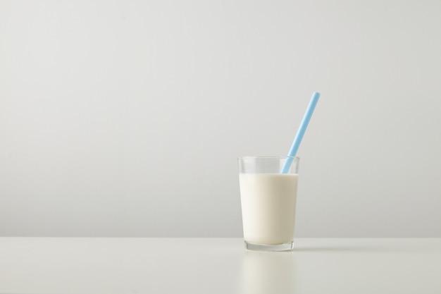Transparant glas met verse biologische melk en blauw rietje binnen geïsoleerd aan de zijkant van de witte tafel