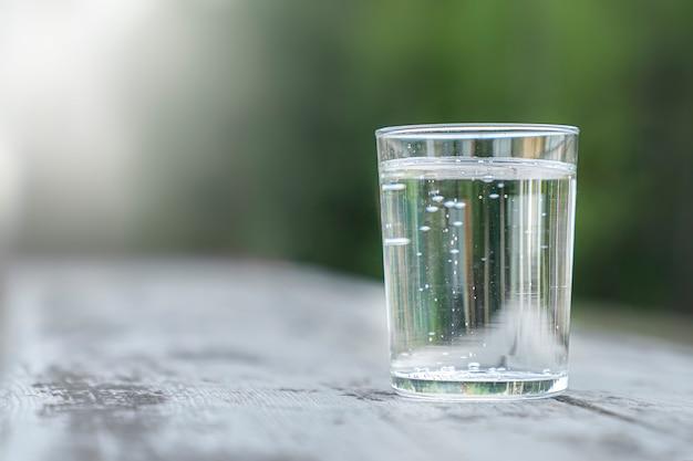 Transparant glas met zuiver mineraalwater op een groene natuurlijke onscherpe ruimte. buitenshuis