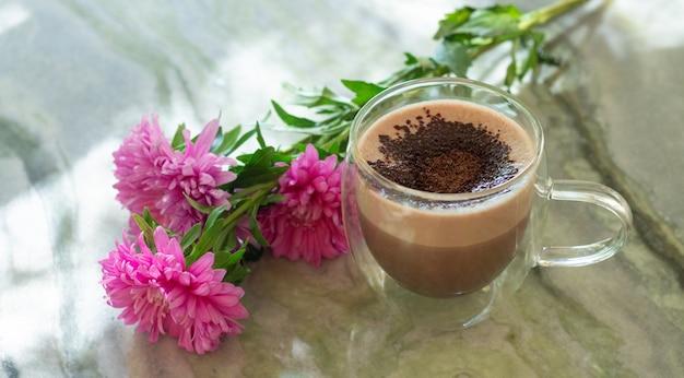 Transparant glazen kopje cacao naast bloemen op marmeren tafel