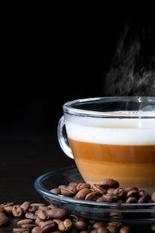 Transparant glazen kopje cappuccino met zichtbare lagen koffie, melk en schuim en bonen op zwart