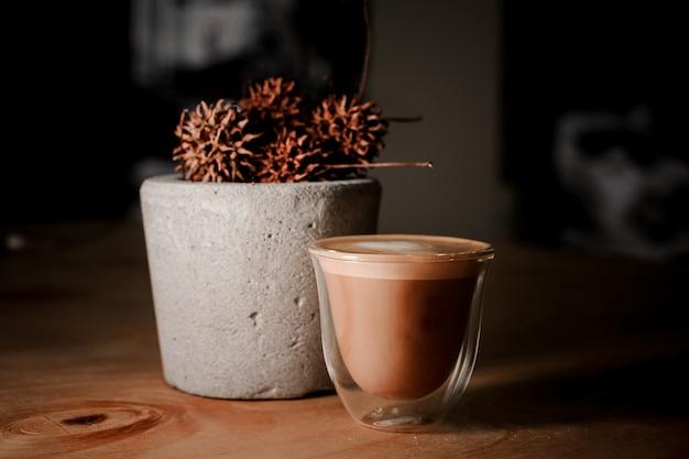 Transparant glazen kopje koffie in de buurt van de betonnen pot met gedroogde planten