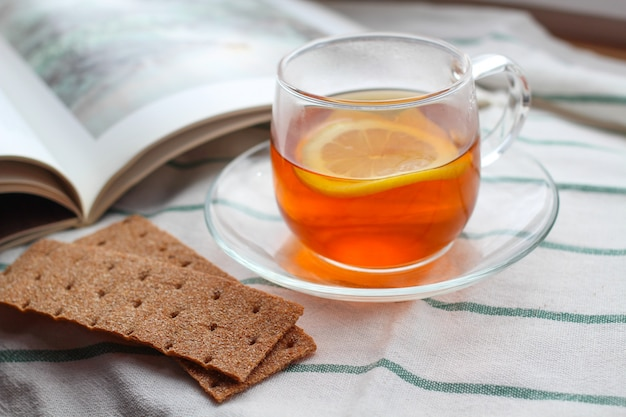 Transparant kopje thee met citroen, rogge knäckebröd, een boek, natuurlijk licht, ontbijt