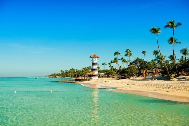 Transparant zeewater en heldere hemel. vuurtoren op een tropisch zandeiland met palmbomen.