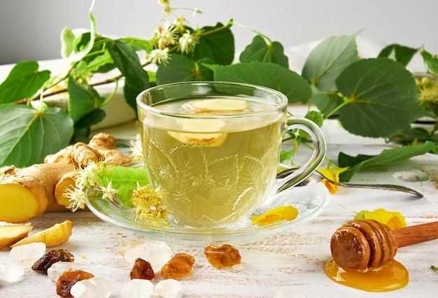 Transparante beker met thee van gember en linden op een witte houten plank