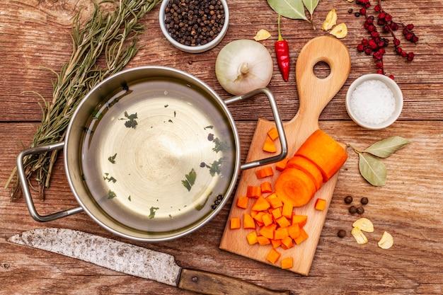 Transparante eendenbouillon in pan met verse ingrediënten. traditionele bouillon voor gezonde gerechten. specerijen, groenten, oude houten tafel
