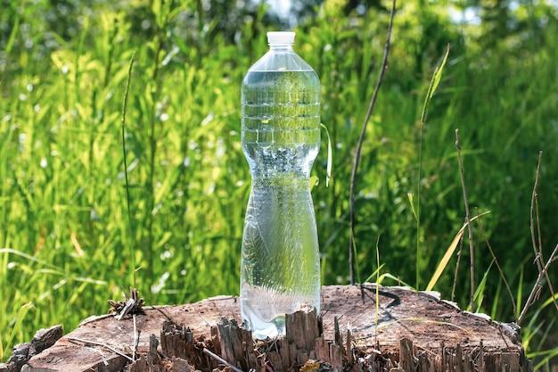 Transparante fles met water op een boomstronk in het gras op de zomer, dorstlesser concept.