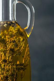 Transparante gele natuurlijke olijfolie met kruiden binnen in dichte omhooggaand van de glasfles.