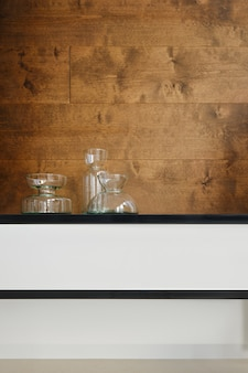 Transparante glazen ddecanters op een plank over houten achtergrond