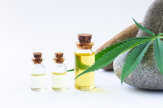 Transparante glazen flessen hennepolie en cannabisblad close-up