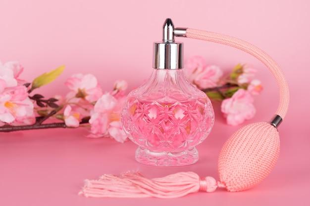 Transparante glazen parfumfles met lente bloeiende boomtak op roze achtergrond. aromatische essentiefles