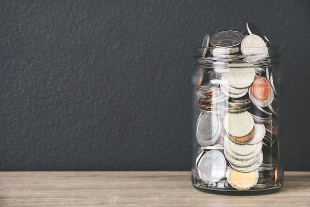 Transparante glazen spaarpot gevuld met munten op houten tafel met zwarte kleur muur achtergrond, kopie ruimte