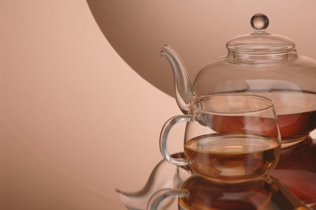 Transparante glazen theepot en kopje thee op het reflecterende oppervlak