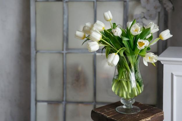 Transparante glazen vaas met boeket bloemen van tulpen op achtergrond