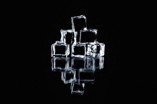 Transparante ijsblokjes gestapelde piramide op zwarte reflecterende achtergrond.