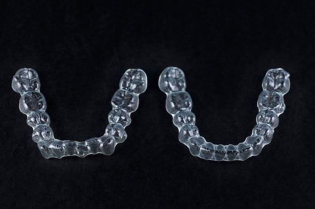 Transparante invisalign-houders op zwarte achtergrond met kopieerruimte