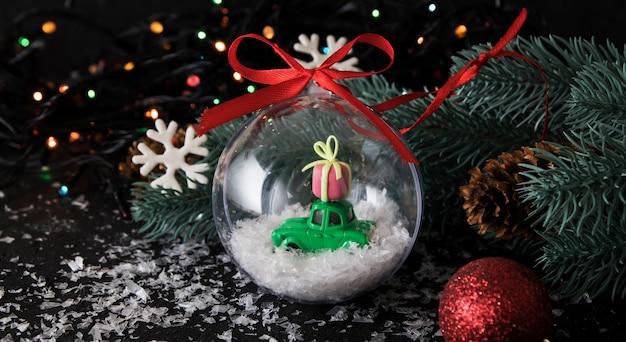Transparante kerstbal met speelgoedauto en cadeau