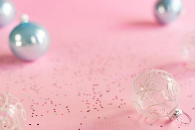Transparante kerstballen en blauwe kerstballen op roze achtergrond met kleurrijke stervormige confetti