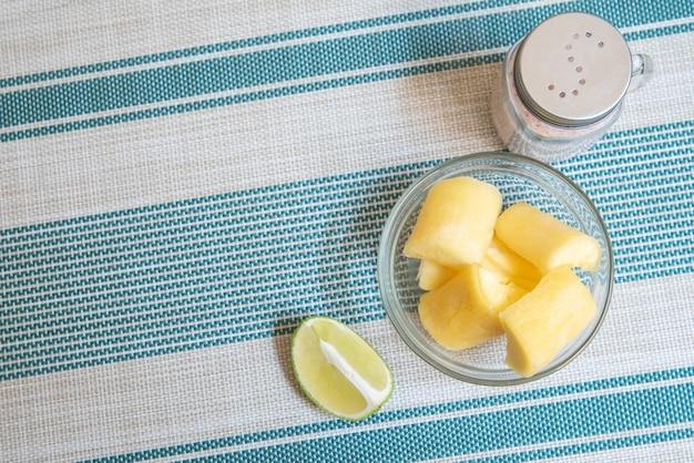 Transparante kom met maniok, citroen en zout op gestreepte achtergrond - hoogste mening