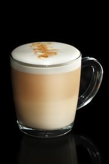 Transparante kopje gelaagde cappuccino geïsoleerd op zwart