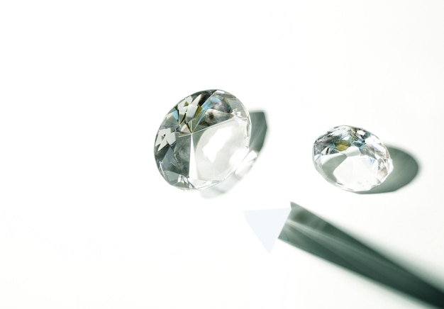 Transparante kristaldiamant die op witte achtergrond wordt geïsoleerd